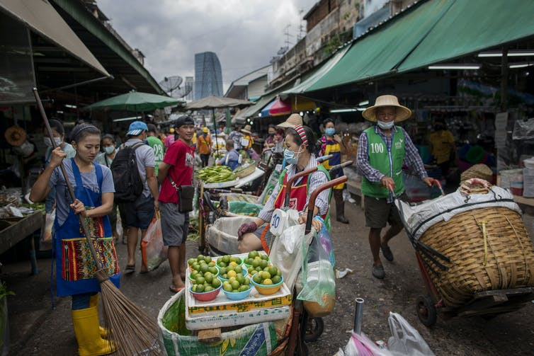 Shoppers and vendors in an open-air market, with fruits and vegetables nearby