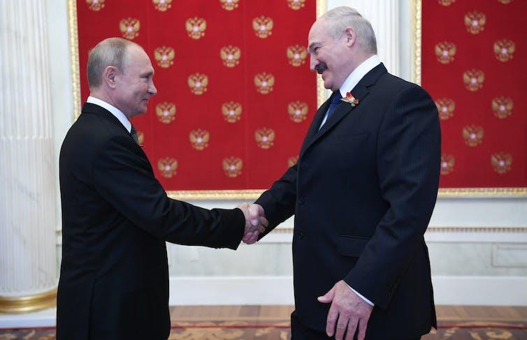 Vladimir Putin and Alexander Lukashenko shaking hands.