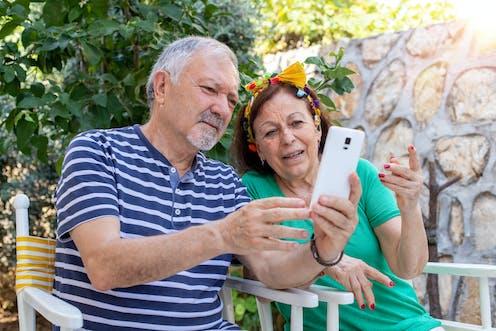 Una pareja madura mira un teléfono móvil.