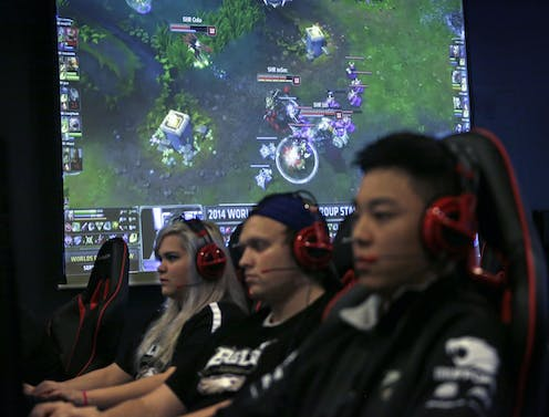 College videogame team members, one female and two male, sit in a row wearing headsets