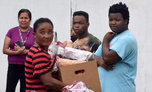 Four people at a food bank, one of whom holds a box of food.