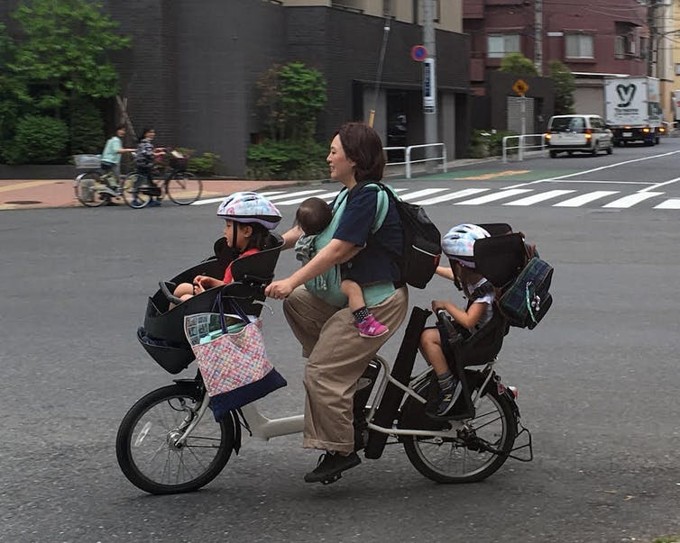 A young woman riding a bike that also holds three young children.