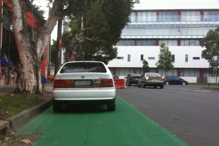 A white car parked in a bike lane.