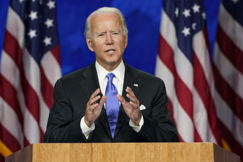 Biden stands at a podium flanked by American flags.