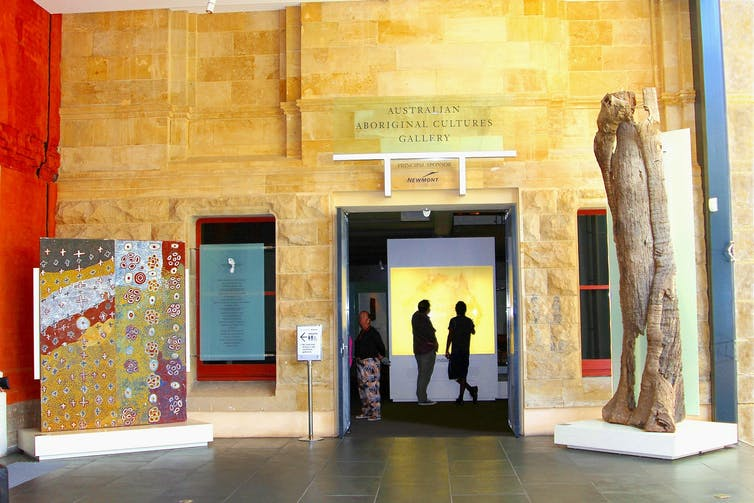 People stand in a gallery among artworks. A sign reads 'Aboriginal Culture Art Gallery'
