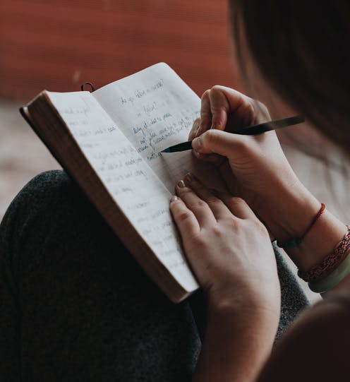 Woman writes in notebook