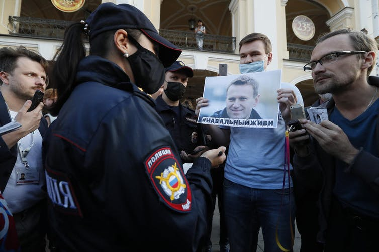 Man surrounded by police and journalists holding photo of Alexei Navalny