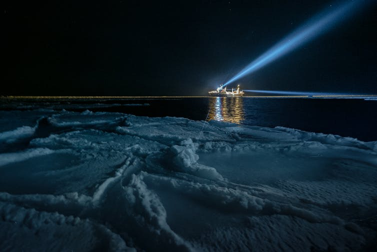 Seen from a sea ice floe, a large ship on the horizon beams white light into the sky.