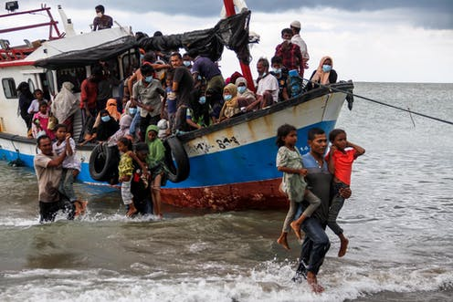 Rohingya refugees evacuated from a boat as they arrive at Lancok beach, North Aceh, Indonesia