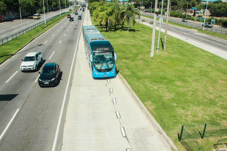 A bus passes through a dedicated lane beside two lanes full of cars.
