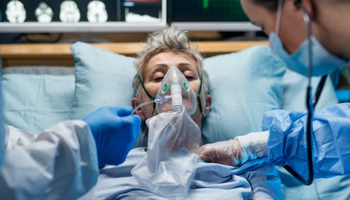 A person in intensive care being given oxygen.