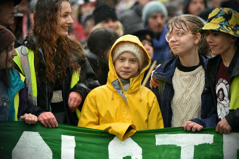 Greta Thunberg stands behind a green banner surrounded by other young activists.
