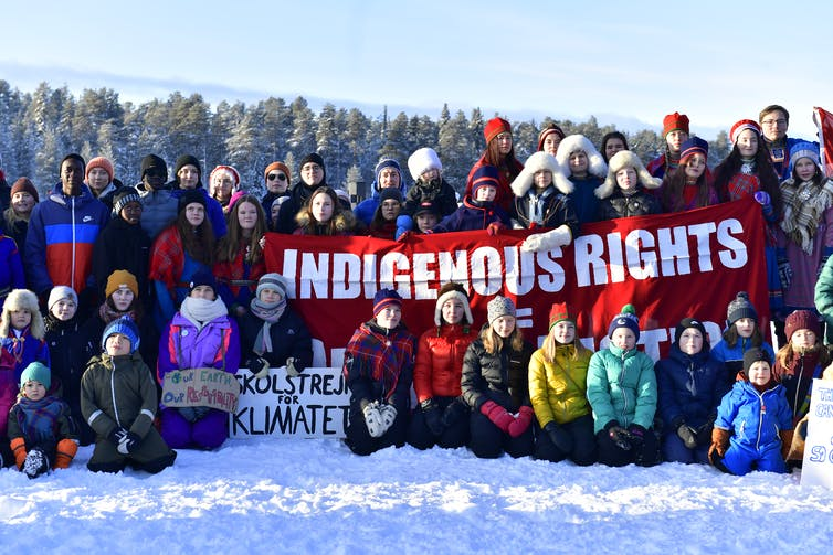 Young Sami people surround a banner reading 'indigenous rights'.