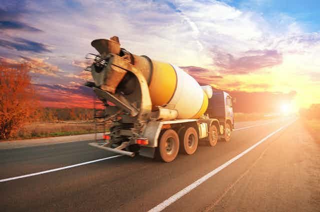 Cement mixer truck drives on road towards sunset