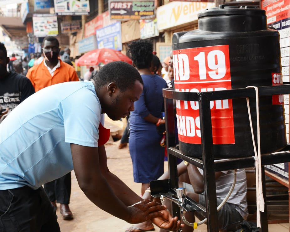Man washing his hands at a disinfection station on the street