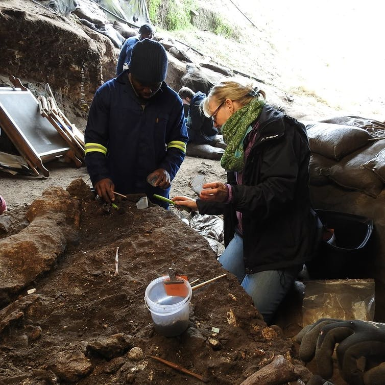 A man and a woman warmly dressed sorting through dug up objects in a cave.