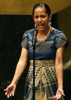 Kathy Jetñil-Kijiner speaks into a microphone.