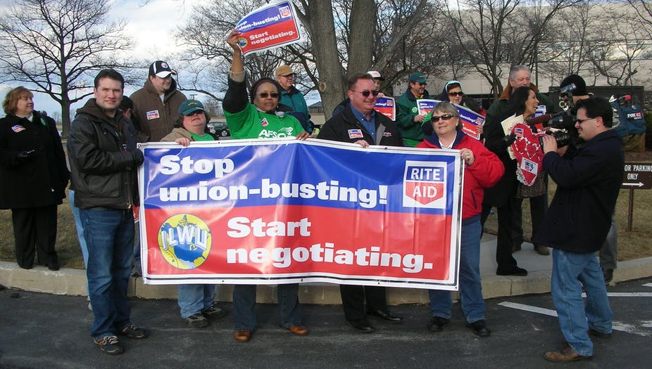 """Protesters carry a sign addressed to Rite Aid that reads """"Stop union-busting! Start negotiating."""""""