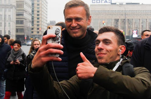 Russian opposition leader Alexei Navalny (L) poses for a photo at a Moscow rally