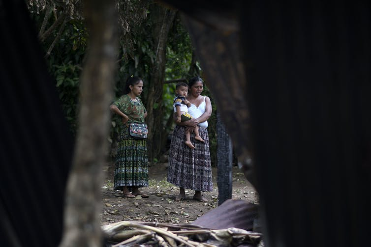 Two women and a child in traditional Indigenous clothing look at a crime scene where a home was burned