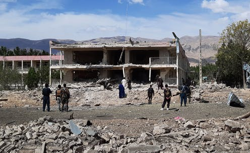 Soldiers and civilians stand in the rubble of a collapsed building with mountains in the background