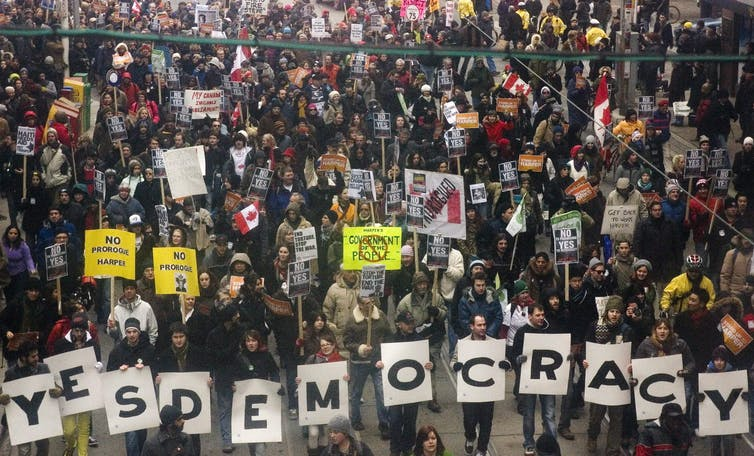 Large crowd of people marching down a street carrying signs that say, 'Yes Democracy'