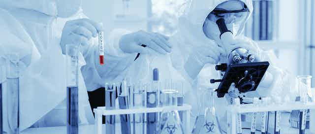 scientist in biohazard protection clothing analyzing covid 19 blood sample with microscope