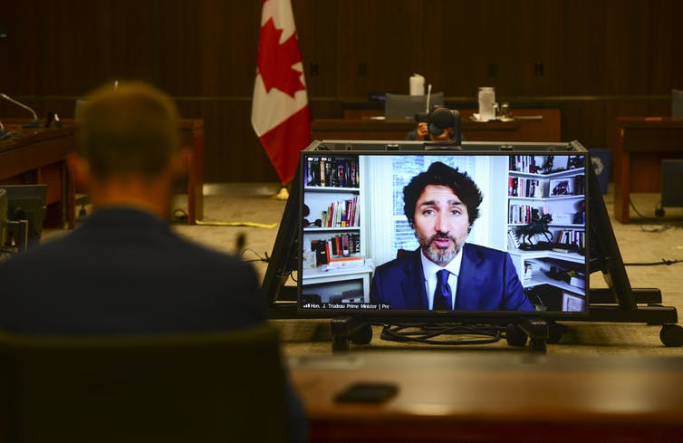 Justin Trudeau seen on a screen in a meeting room