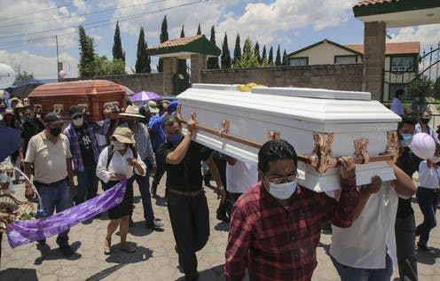 Men in face masks carry two coffins, one white and one mahogany