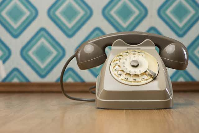Retro phone on wooden floor with retro geometric wallpaper in background