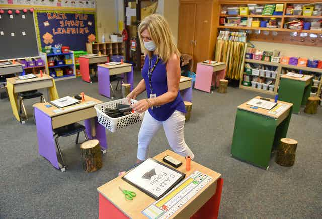 An elementary school teacher prepares her classroom for students, with desks spaced several feet apart.