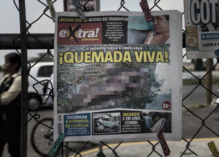 A newspaper front page with blurred out image of a murdered woman's mutilated body, reading 'Burnt Alive!'