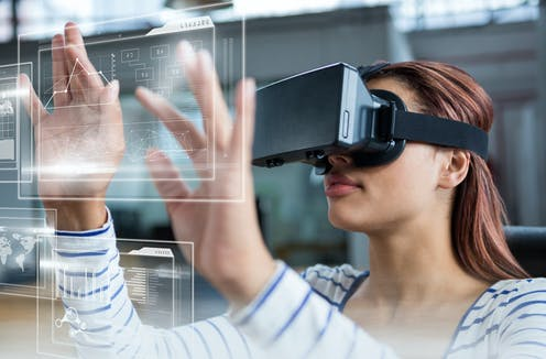 A student in a VR headset touches a screen.
