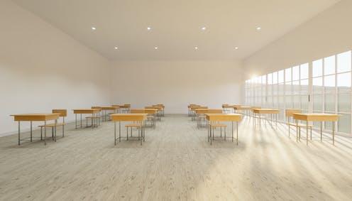 Aula con pocas mesas y sillas y muy luminosa.