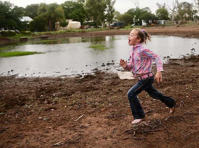 Girl funning on a farm after rain