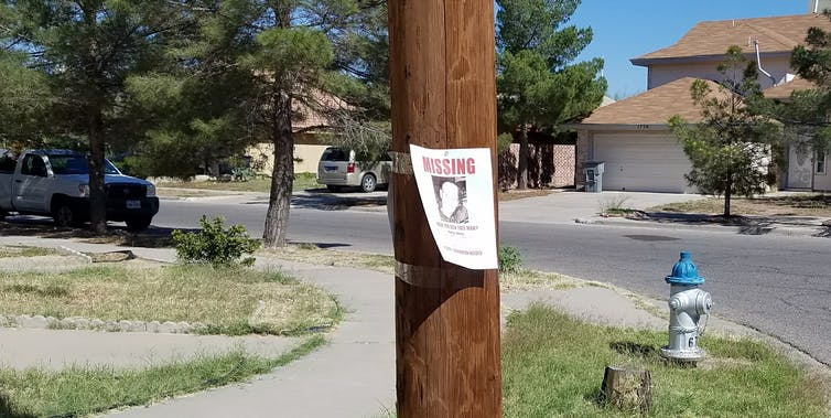 A missing persons sign on a telephone pole.