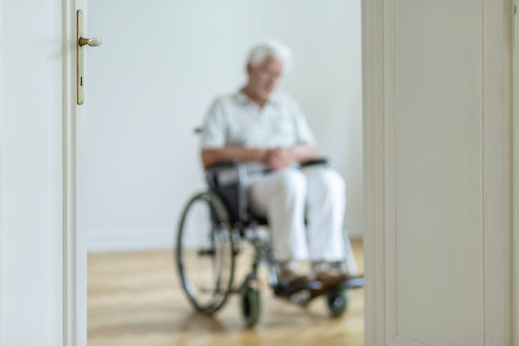 Blurred view of a man sitting in wheelchair through a doorway.