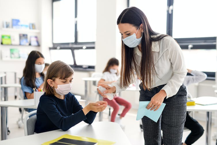 A teacher and student in a classroom wearing face masks.