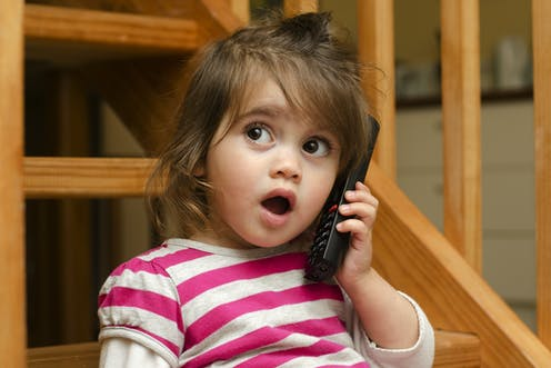 A toddler talks on a phone.