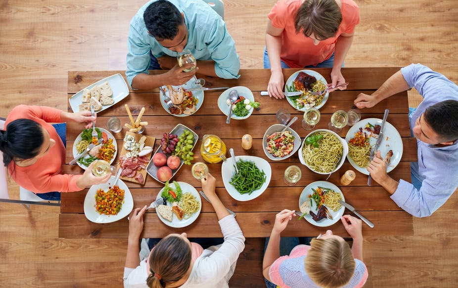 Group of friends eating large meal at a dinner table.