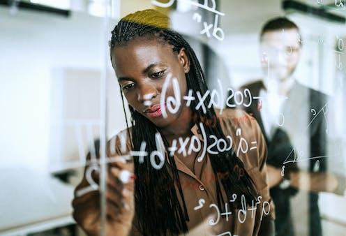 A woman writes a math problem on a glassboard.