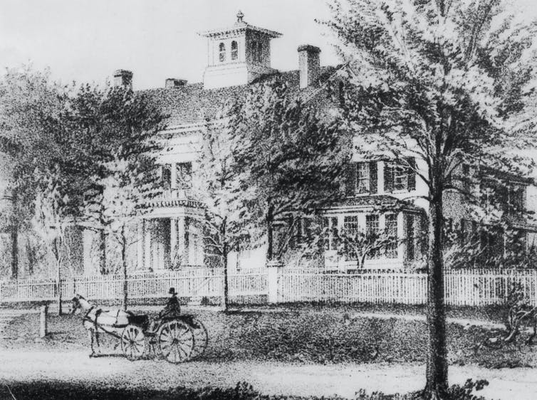 A horse-drawn carriage passes by Emily Dickinson's home in Amherst, Mass.