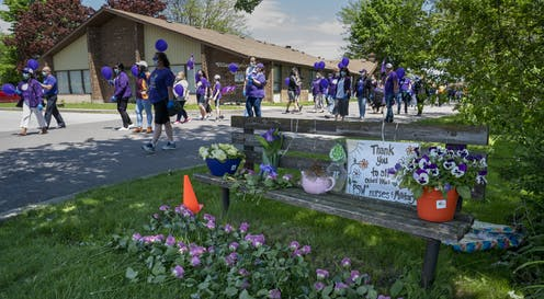 Nurses dressed in purple and carrying purple balloons march in front of a long-term care home.