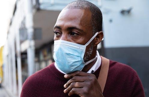 A Black British man wearing a mask