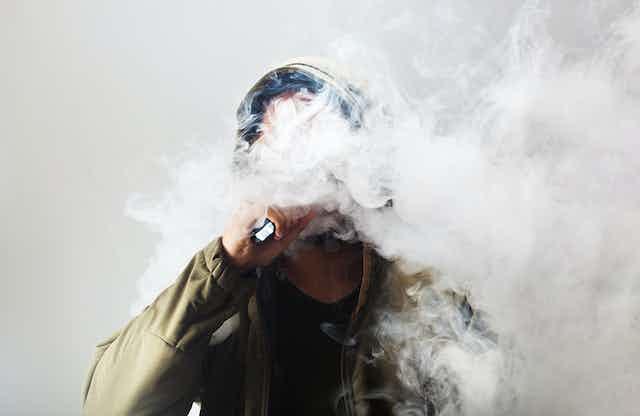 Man in a cloud of vape smoke