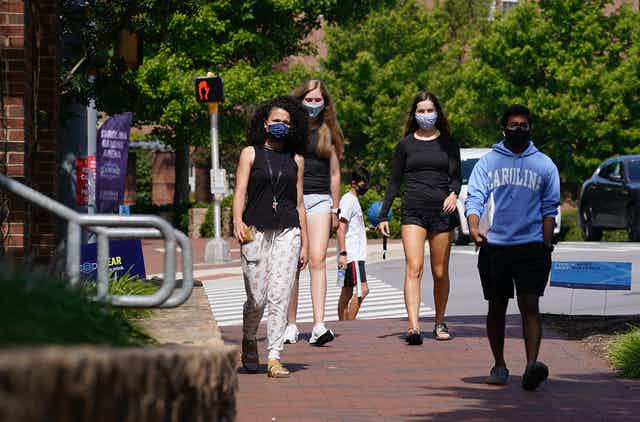 Four college students wearing masks walk down a brick path
