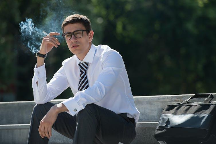 Un homme en complet cravate est en train de fumer assis sur des marches publiques.