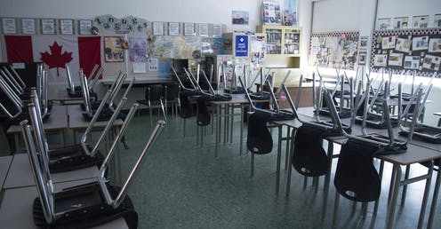Chairs are seen on desks in an empty and dark classroom.