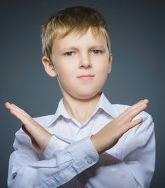 A boy in while shirt crossing his arms in front of him into an x shape.