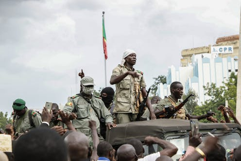 Soldiers in fatigues ride atop a jeep, with a Malian flag and large building in the background